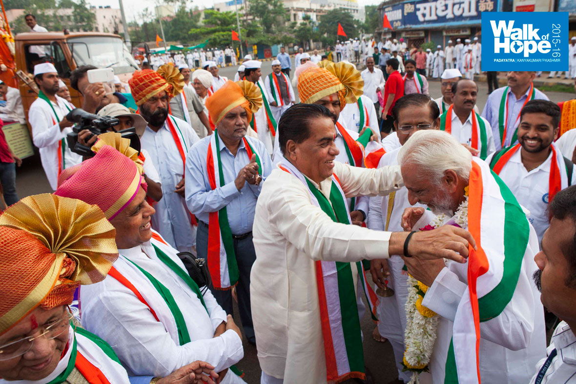 10.Sir-being-draped-with-a-tri-colour-sash-in-probably-the-most-colourful-reception-so-far,-Kolhapur,-Maharashtra)