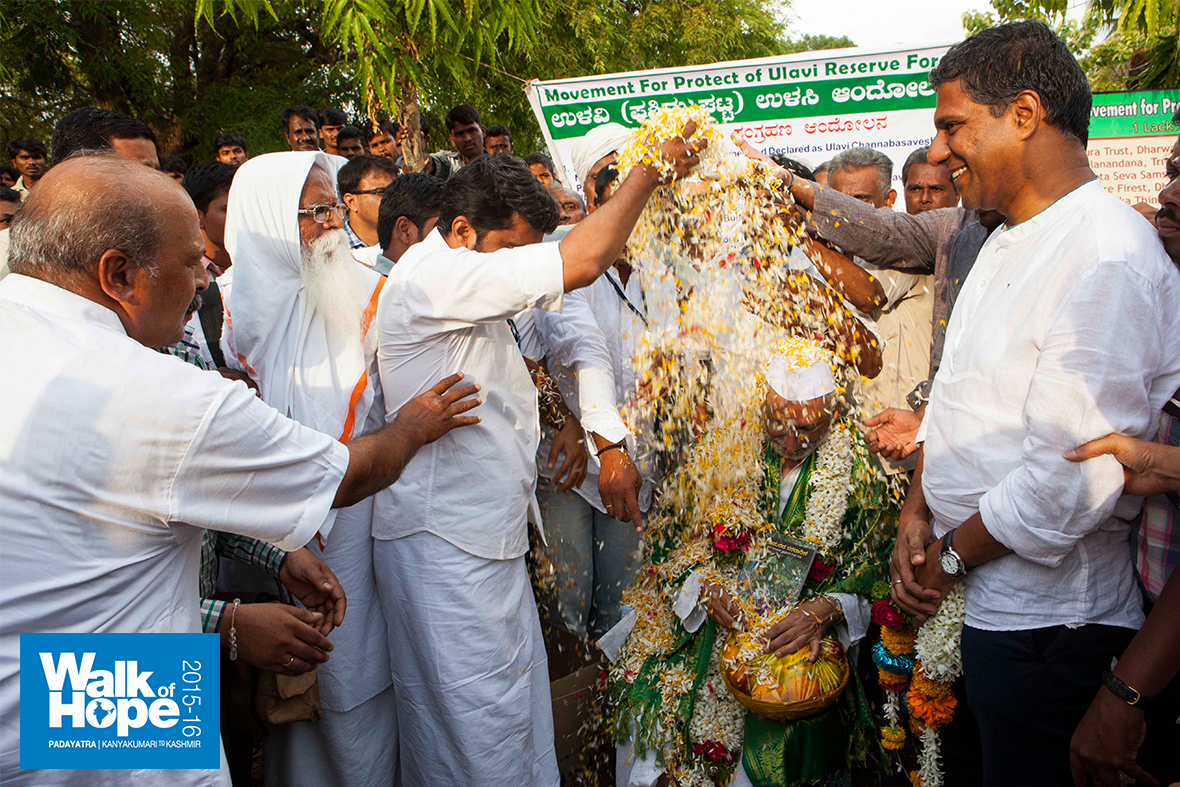 6.Sir-being-showered-with-flower-petals-on-arrival-at-the-Ulavi-Temple,-Dharwad,-Karnataka