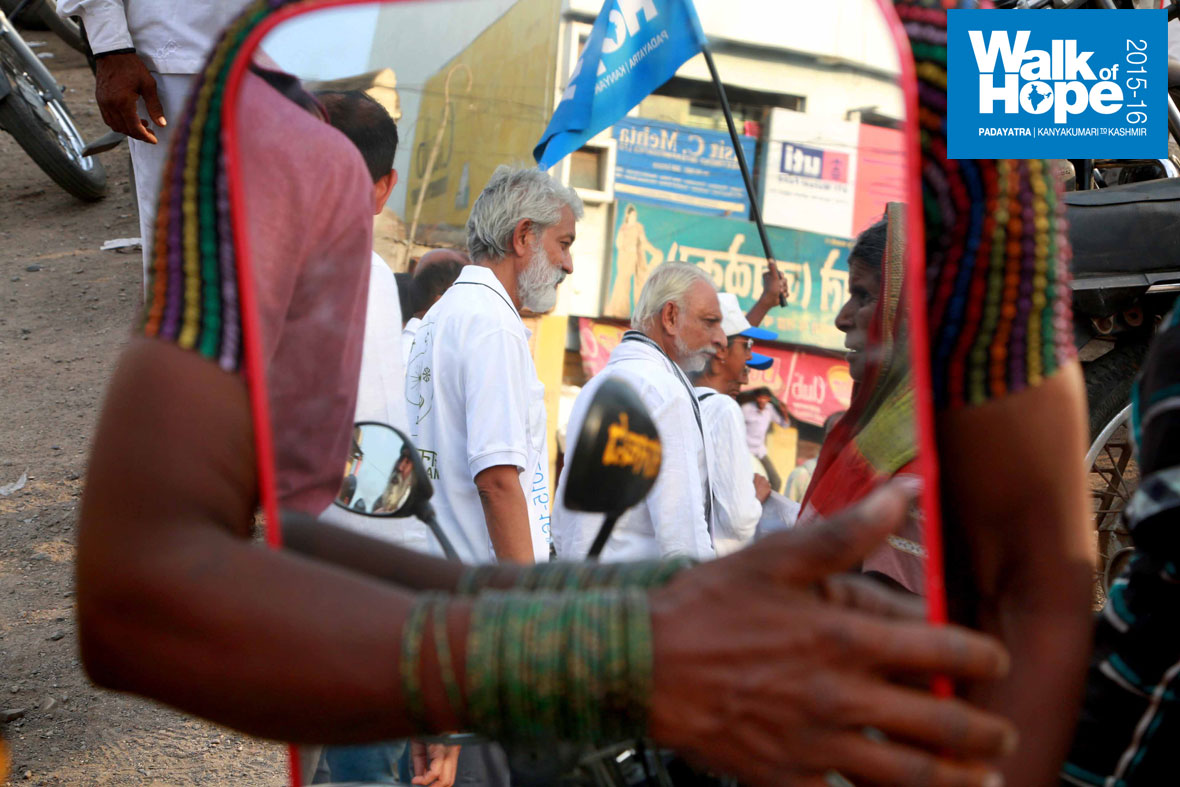 8.Sir-and-some-Padayatris-cast-their-benign-reflection-on-a-mirror-on-sale,-Mangalvedha,-Solapur,-Maharashtra