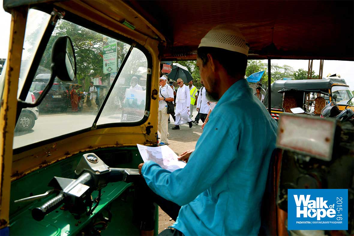 8.The-autowala-has-a-quick-look-at-our-flyer-as-he-waits-for-the-Padayatra-to-pass,-Marol-Rasta,-Gujarat
