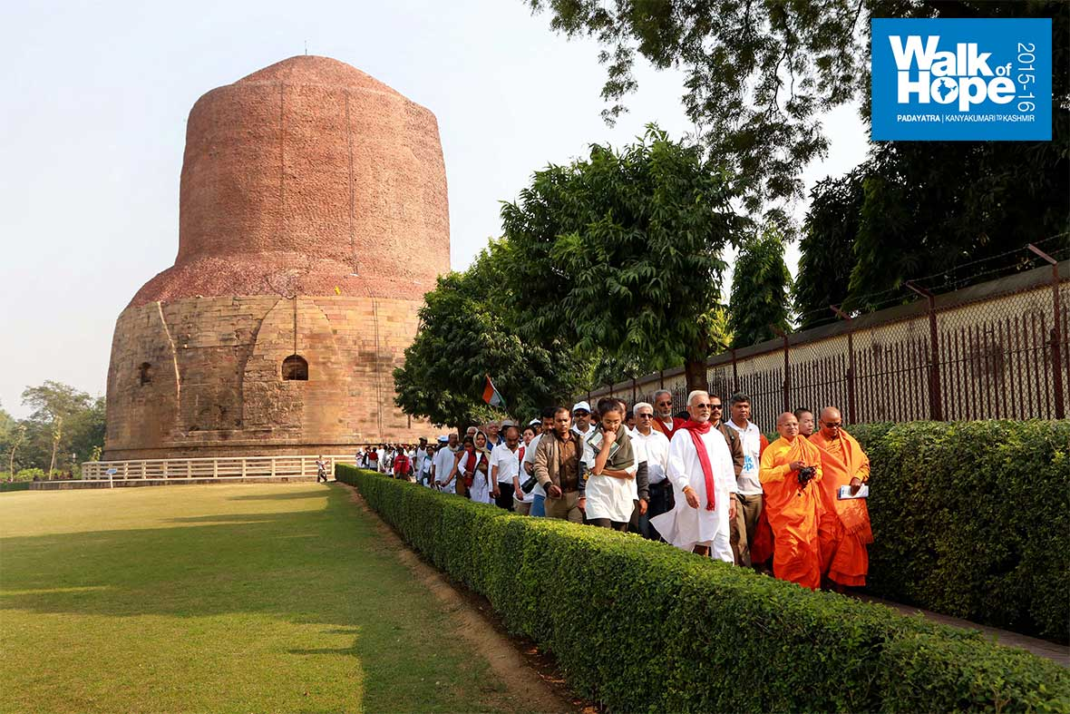 3.Yatris-tread-hallowed-ground-with-the-magnificent-Dhamek-Stupa-in-the-background,-Sarnath,-Varanasi,-UP